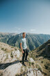 Vertical shot handsome bearded Caucasian man on a rocky mountain