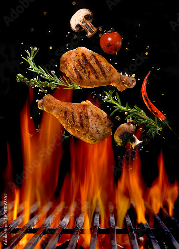 Chicken legs and spicy ingredients flying above flaming red barbeque grill