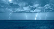 Beautiful Landscape With Lightning Over The Calm Sea At Sunset