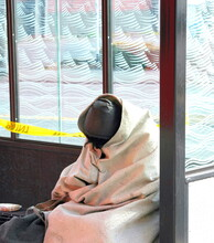 Homeless Man Sleeping At A Bus Stop Outside Where A Man Was Killed.