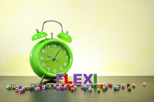Flexible Time Concept.  Block Letters On Flexi With Colorful Cubes And An Alarm Clock At The Back
