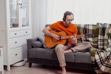 Young Caucasian Man In Headphones Playing The Guitar Sitting On Couch At Home. Practice Music, Lifestyle Photo