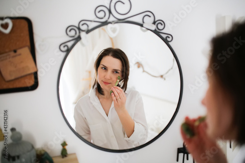 Cute caucasian woman with Jade Massage Roller near mirror ,female brunette does facial massage with roller, gouache Poster Mural XXL