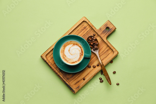Fototapeta Cup of hot cappuccino and spoon with coffee beans on color background obraz