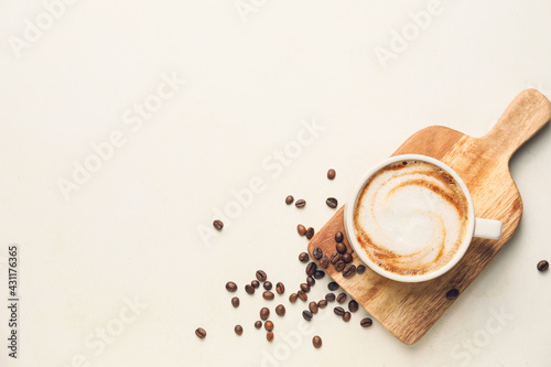 Fotografiet Cup of hot cappuccino on light background
