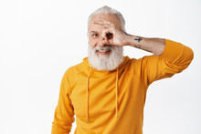Happy Old Man With Tattoos Showing Okay Sign, Looking Through OK Fingers And Smiling Pleased, Satisfied, Praise Something Good, Say Yes Or Alright, Standing Over White Background