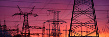 View Of High Voltage Pole Power Transmission Tower On Sunset. Panorama High Voltage Tower With Power Lines.