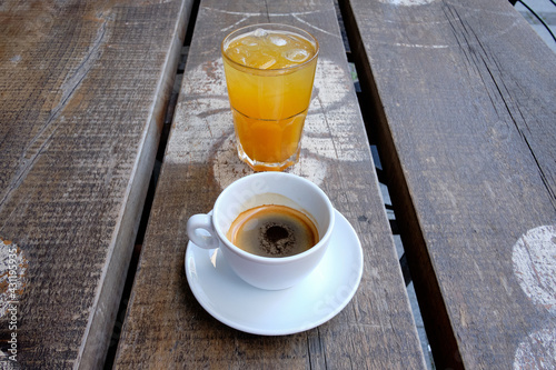 Obraz Cup of coffee and a glass of fresh orange juice on a wooden board - fototapety do salonu