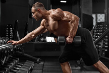 Muscular Man Working Out In Gym Doing Exercise For Back. Single Arm Dumbbell Row