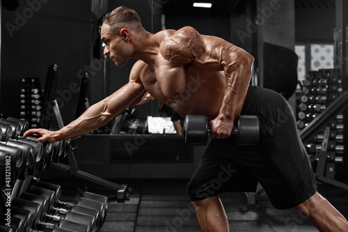 Canvas Muscular man working out in gym doing exercise for back