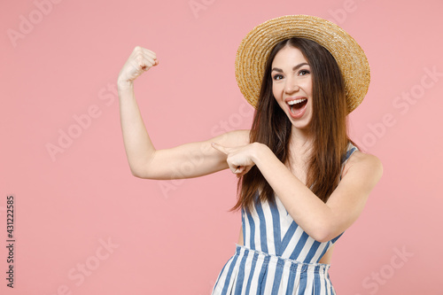 Young woman in summer clothes striped dress straw hat put arm on biceps muscles on hand demonstrating strength power isolated on pastel pink color background studio portrait Fototapete