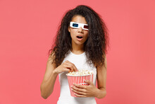 Young Shocked Scared Amazed African Woman 20s Wear 3d Glasses Watch Movie Film Hold Akeaway Bucket Of Popcorn Isolated On Pink Background Studio Portrait. People Emotions In Cinema Lifestyle Concept.