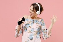 Young Caucasian Woman With Short Hairdo Wear Trendy Stylish Blouse Headphones Listen To Music Dancing Sing Song Record Voice By Mobile Cell Phone Dictaphone Isolated On Pastel Pink Background Studio