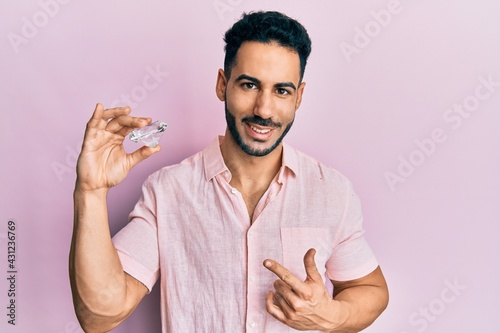 Fotografie, Tablou Young hispanic man holding brilliant diamond stone smiling happy pointing with h