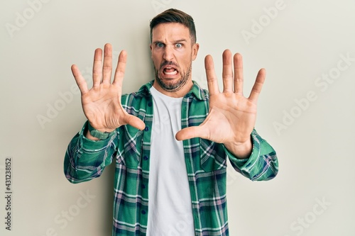 Foto Handsome man with beard wearing casual clothes afraid and terrified with fear expression stop gesture with hands, shouting in shock