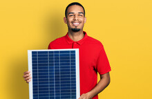 Young African American Man Holding Photovoltaic Solar Panel Smiling With A Happy And Cool Smile On Face. Showing Teeth.