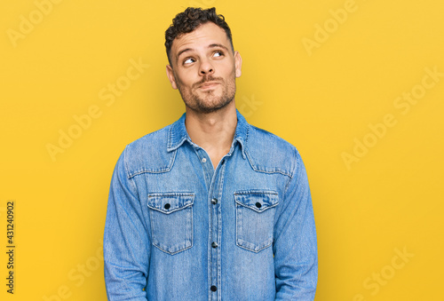 Canvas Print Young hispanic man wearing casual denim jacket smiling looking to the side and staring away thinking
