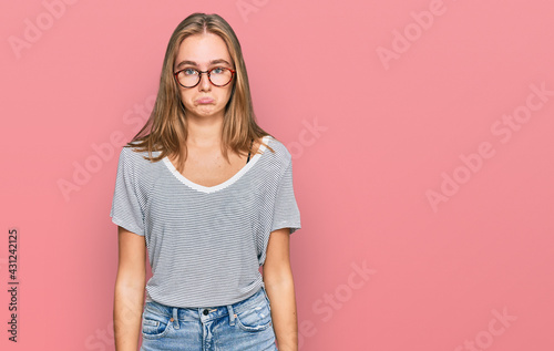 Foto Beautiful young blonde woman wearing casual clothes and glasses depressed and worry for distress, crying angry and afraid