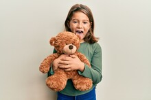 Little Beautiful Girl Hugging Teddy Bear Sticking Tongue Out Happy With Funny Expression.