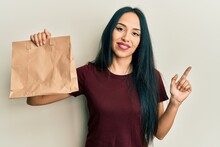 Young Hispanic Girl Holding Take Away Paper Bag Smiling Happy Pointing With Hand And Finger To The Side
