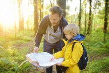 Schoolchild And His Mature Father Hiking Together And Exploring Nature. Little Boy With Dad Looking Map During Orienteering In Forest. Adventure, Scouting And Hiking Tourism For Kids.