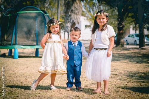 Slika na platnu Hermanos infantes corren agarrados de la mano con felicidad en un parque