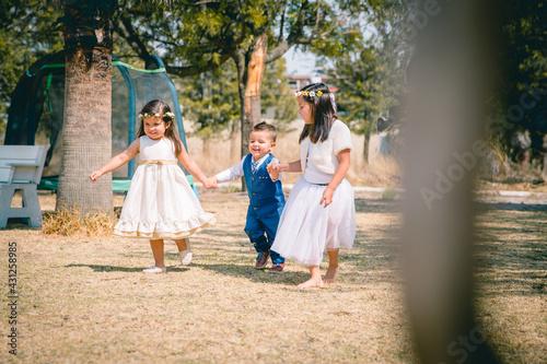 Hermanos infantes corren agarrados de la mano con felicidad en un parque Fototapeta