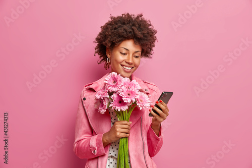 Fototapeta Glad Afro American lady in stylish clothes checks messages online gets congratulations on birthday holds beautiful bouquet of gerberas has happy mood isolated over pink background