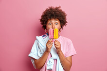 Stunned Curly Haired Ethnic Teenage Girl Covers Mouth With Two Frozen Ice Creams Has Sweet Tooth Enjoys Eating Yummy Summer Dessert Wears Casual T Shit And Jumper Isolated Over Pink Background