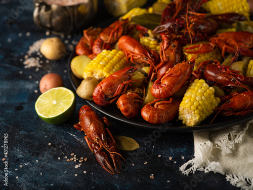 Boiled crayfish with potatoes and corn. With lemon and lime. On a dark blue table. Various recipes and recipe book
