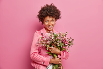 Cute curly haired African American woman embraces big bouquet of flowers recieved from boyfriend has festive mood wears jacket isolated over pink background. Holiday event. Mothers Day concept