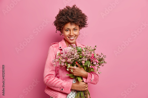 Canvas Print Cute curly haired African American woman embraces big bouquet of flowers recieved from boyfriend has festive mood wears jacket isolated over pink background