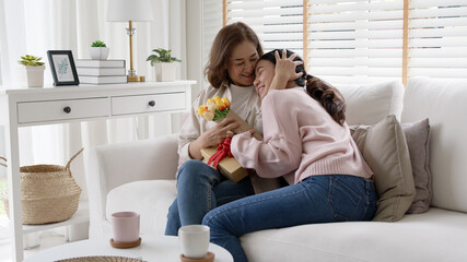 Attractive beautiful asian middle age mum sit with grown up daughter give gift box and flower in family moment celebrate mother day. Overjoy bonding cheerful kid embrace relationship with retired mom.