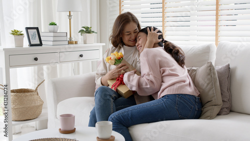 Attractive beautiful asian middle age mum sit with grown up daughter give gift box and flower in family moment celebrate mother day. Overjoy bonding cheerful kid embrace relationship with retired mom. - fototapety na wymiar