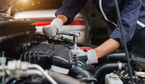 Automobile mechanic repairman hands repairing a car engine automotive workshop with a wrench, car service and maintenance,Repair service. - fototapety na wymiar