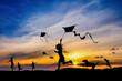 Grupa dzieci puszczających latawca o zachodzie słońca