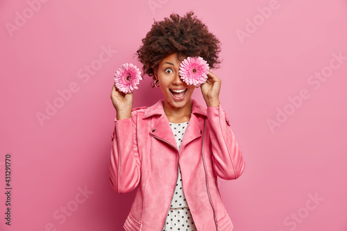 Fototapeta Positive female florist covers eyes with fragrant gerbera flowers makes bouquets for special occasions smiles broadly wears fashionable jacket isolated over pink background. Feminity concept. obraz