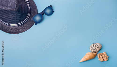 Obraz Flat lay of shells and hat on a blue background - fototapety do salonu
