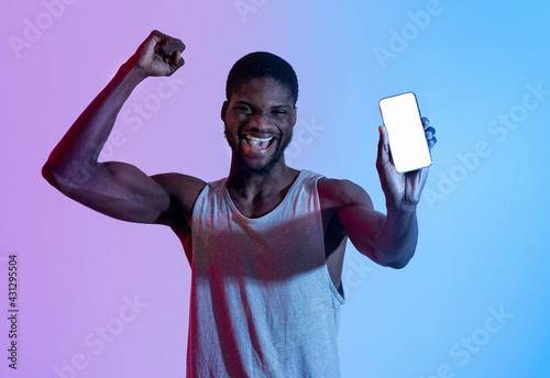 Fototapeta premium Excited black athlete showing cellphone with blank screen, making YES gesture in neon light, mockup for design