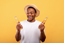 Portrait Of Excited Black Man Holding Two Bottles Of Refreshing Cool Beer, Having Beach Party On Yellow Background
