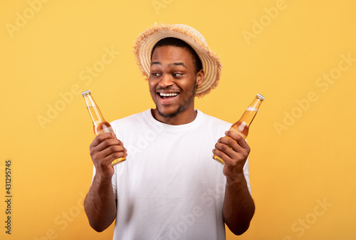 Canvas Print Portrait of excited black man holding two bottles of refreshing cool beer, havin