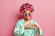 Horizontal Shot Of Pretty Satisfied Afro American Woman Applies Hair Rollers For Making Hairstyle Wears Silk Dressing Gown Sunglasses And Earrings Shapes Heart Sign Isolated Over Pink Background.