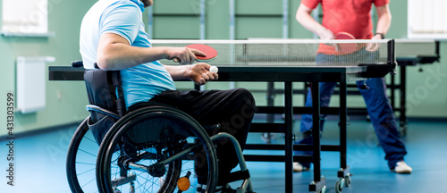 Adult disabled man in a wheelchair play at table tennis with his coach - fototapety na wymiar