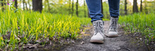 Hiking Boot On Footpath. Panoramic View Of Hiker Legs Walking At Woodland
