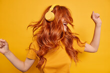 Cool Millennial Girl Keeps Arms Raised Dances Carefree Enjoys Every Bit Of Music Wears Wireless Headphones On Ears Has Red Hair Floating On Wind Dressed In Casual T Shirt Isolated Over Yellow Wall