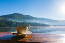 Hot Coffee Latte In Coffee Cup With Beautiful View In Morning Sunrise Light At Ban Rak Thai, Mae Hong Son, Thailand.