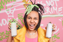 Modern Teenage Girl Has Dreadlocks Looks With Cheeky Face Expression At Camera Holds Two Aerosol Bottles For Drawing Graffiti Dressed In Fashionable Clothes. Millennial Generation. Grunge Style