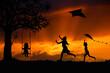 Sylwetki dzieci bawiących się latawcami i na huśtawce