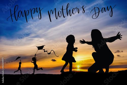 Sylwetka matki i dzieci na tle zachodzącego słońca, dzień matki. - fototapety na wymiar