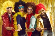 Pop Music Band Singing At Night Club. Young People Disguised In Fancy Feather Boas And Funny Silly Curly Wigs Dancing Together. Happy Multiethnic Men And Women Having Fun At Halloween Disco Party